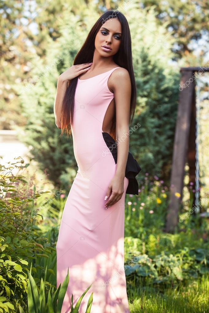 Outdoors portrait of beautiful young brunette girl in luxury dress posing in summer garden.