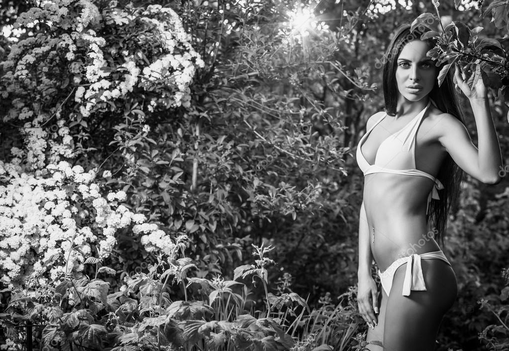 Suntanned attractive beauty dressed bikini poses in autumn garden. Black-white photo.