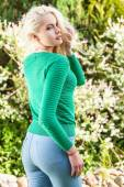 Fényképek Outdoors portrait of beautiful  positive young blond girl in stylish green sweater. Person against nature.