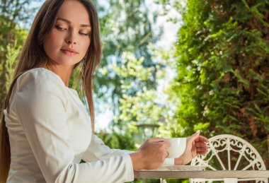 Outdoors portrait of beautiful young girl in luxury white dress posing near garden metal table with cup of coffee.