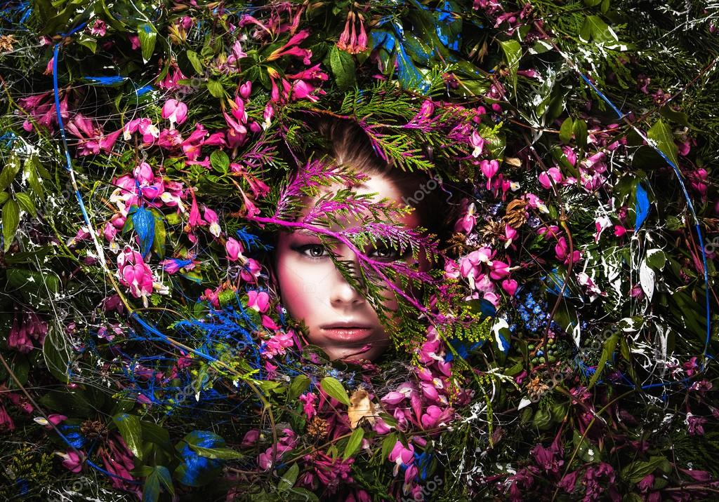 Fairy tale girl portrait surrounded with natural plants and flowers. Art image in bright fantasy stylization.