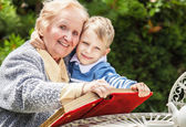 Positive grandmother and grandson spent time together in summer solar garden.