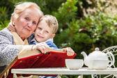 Positive grandmother and grandson spent time together in summer solar garden.
