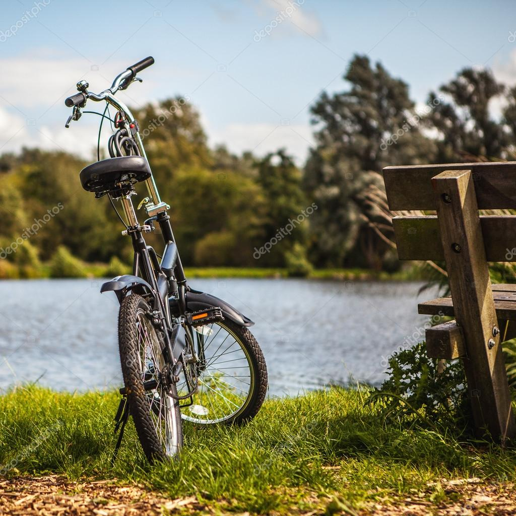 Bicycle near bench and pond