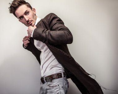 Elegant young handsome man in long stylish coat. Studio fashion portrait. stock vector