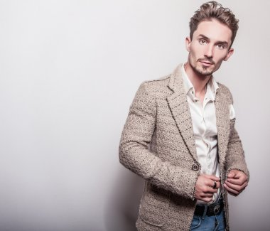Elegant young handsome man in stylish beige costume. Studio fashion portrait. stock vector