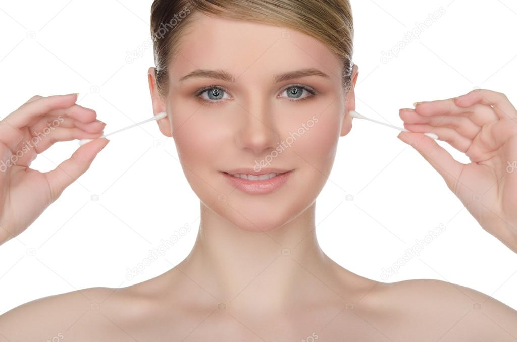 Beautiful woman cleans ears with cotton sticks isolated on white