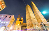 Photo Ancient Asinelli Towers at night with church in Bologna, Italy