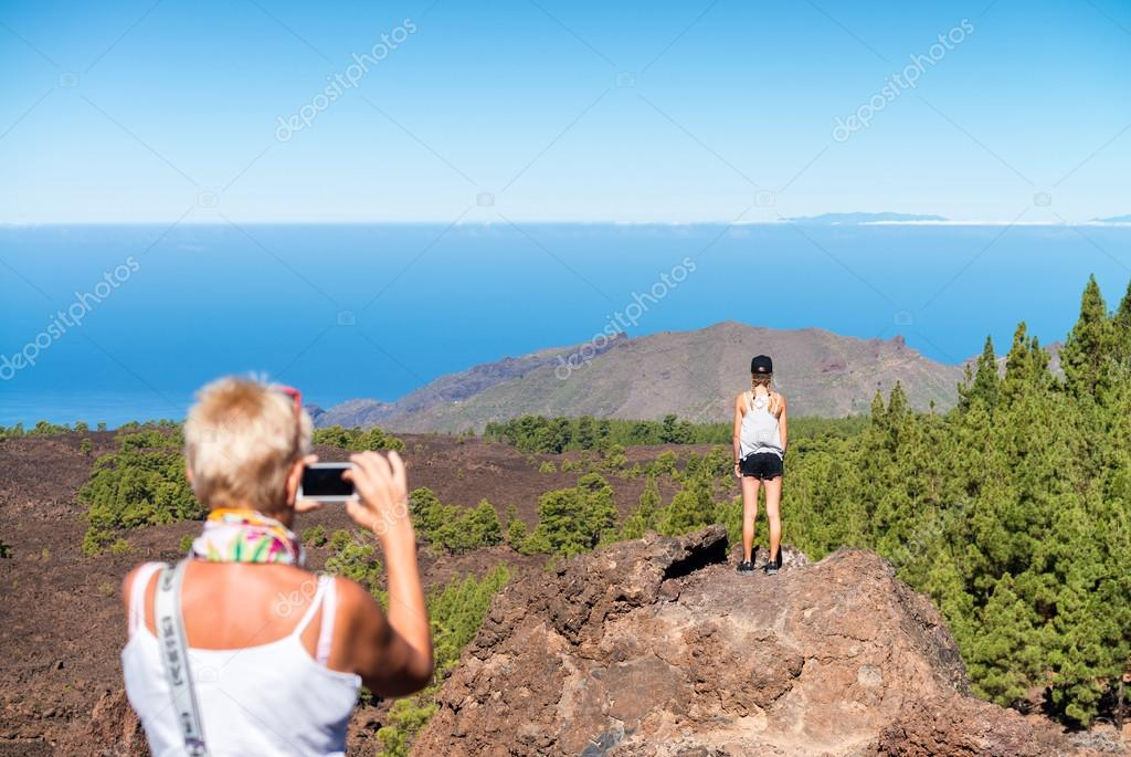 Back view of mother taking a picture of daughter on a mountain