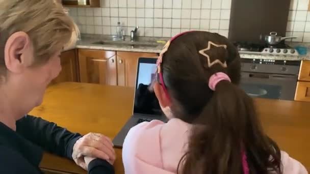 Young girl with her grandma on a videocall with their parents