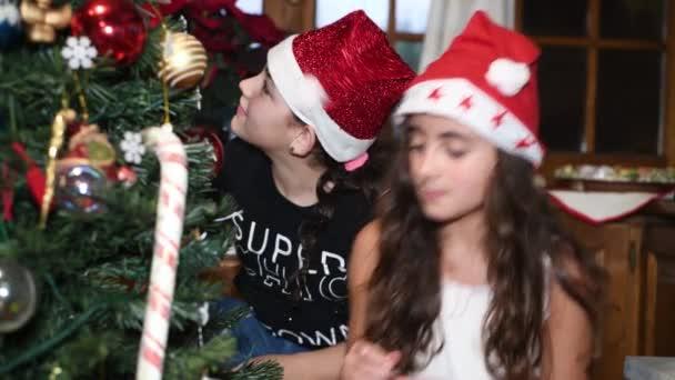 Két fiatal lány otthon karácsonyfát díszít Mikulás sapkában. Lassú mozgás.