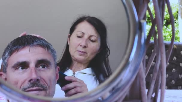 Haircut at home. Female hairdresser combing hair to her husband with mrror reflections