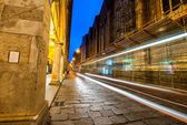 Photo Illuminated street of Bologna at night with bus light trails