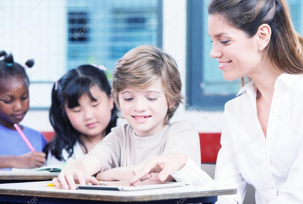 Teacher with schoolboy in a multi ethnic elementary classroom