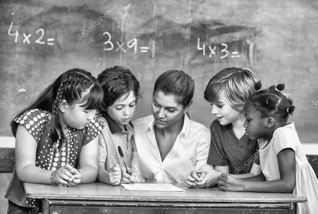 Attractive young female teacher checking multi race classroom wo