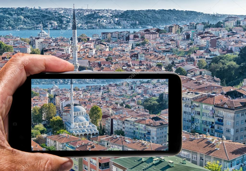 Male hand with smartphone taking a picture of Istanbul. Tourism