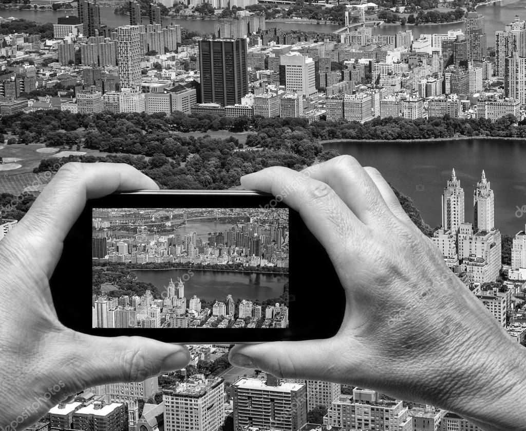 Man and woman hand capturing New York aerial skyline with smartp
