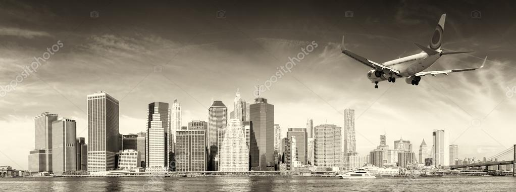 Black and white view of airplane over New York City. Tourism con
