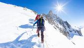 Fotografia Alpinisti scalare una vetta nevosa. In fondo la famosa vetta D