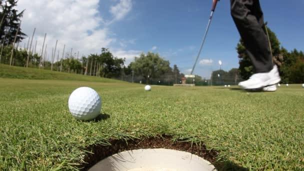 Golfista vyhnal míč do díry na putting green; letní slunečný den, selektivní zaměření na míč