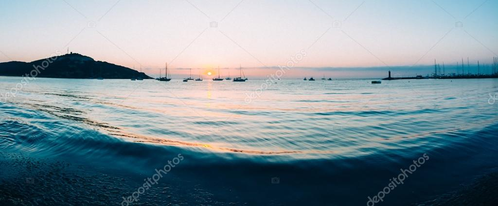 Sunrise on a small bay with anchored sailboats.