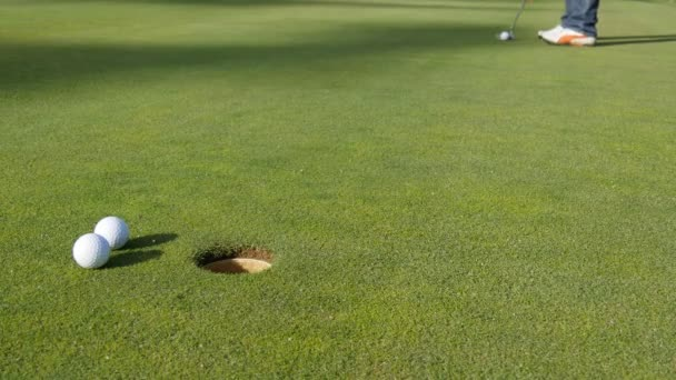 Golfer putting golf ball into hole