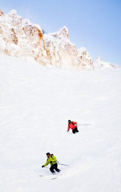 Two skiers going downhill