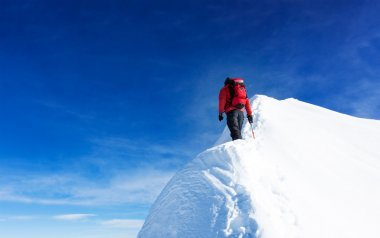Mountaineer reach the summit of a snowy peak. Concepts: determin