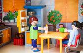 Kleine Kunststoff-Spielzeug. Mutter bereitet Eatlittle Plastikspielzeug. Mutter bereitet Essen