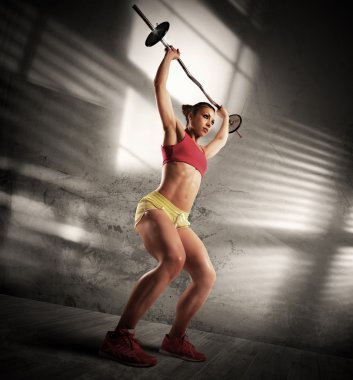 Woman is training with barbell