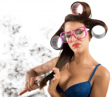 Girl with curlers combing hair
