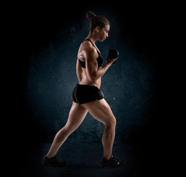 Muscular woman with dumbbell