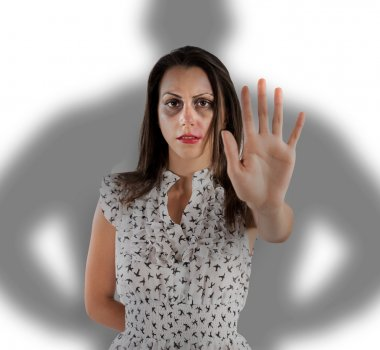 Scared woman with bruises and scratches with shadow of a man behind her. stop gesture stock vector