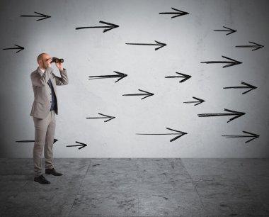 Man looking  through binoculars with arrows