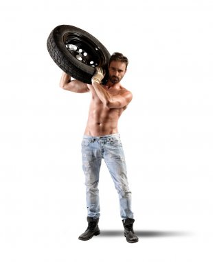 Car mechanic carrying a tire