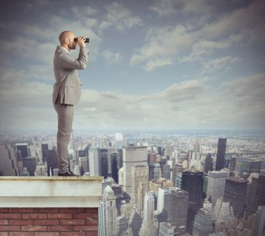 Businessman looks beyond with his binoculars