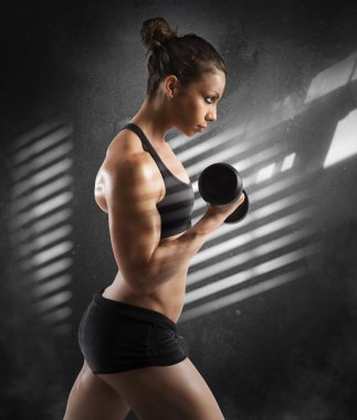 woman training her biceps with dumbbells