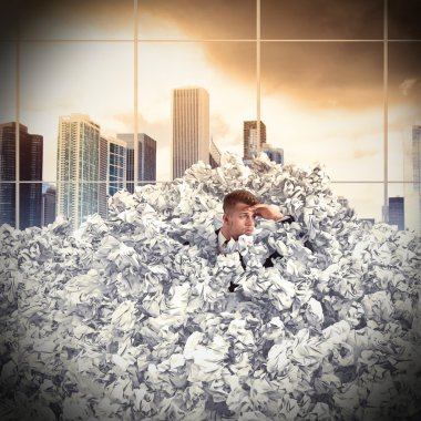 businessman buried by balls of paper