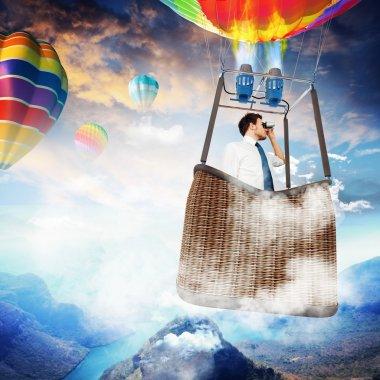 Businessman with binoculars in hot air balloon