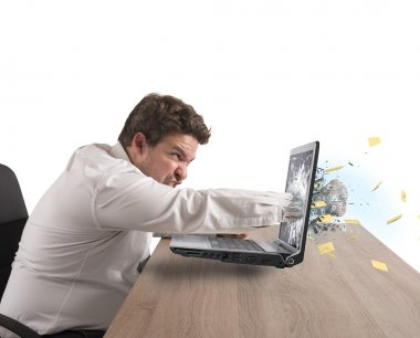 businessman give a punch to laptop computer