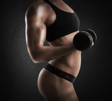 woman is training with a dumbbell