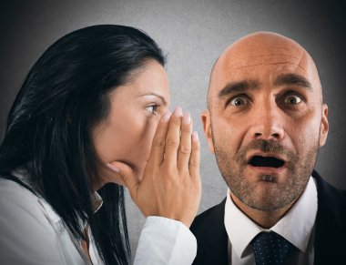 Woman talking in secret to a man