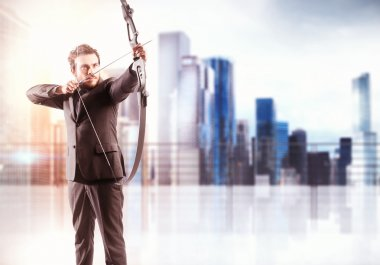 businessman with bow pointing a target