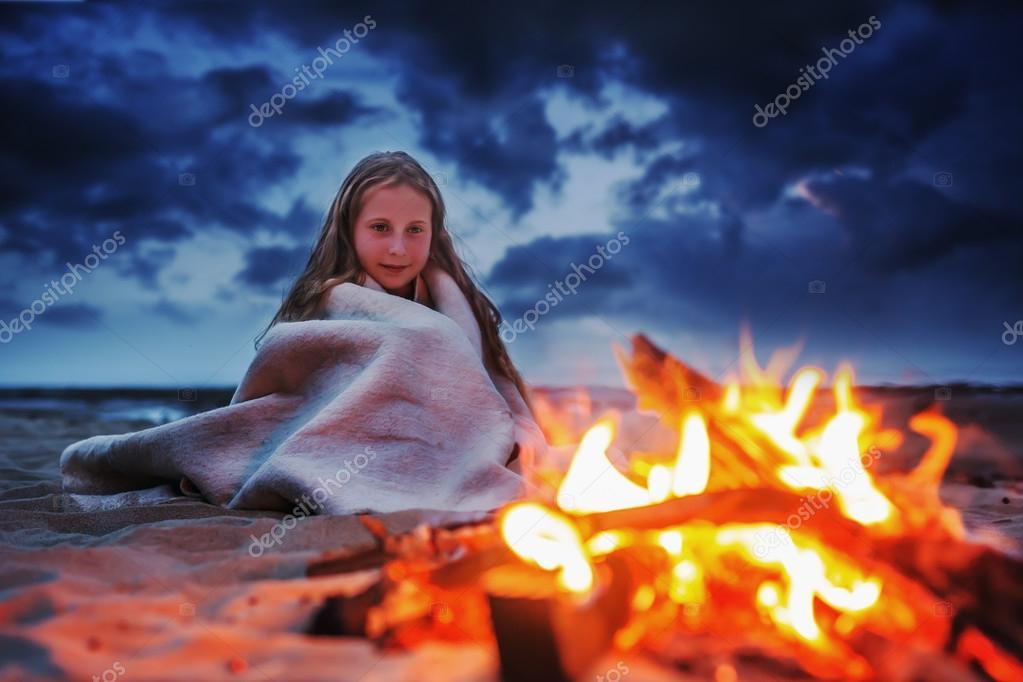 Girl near camping fire.