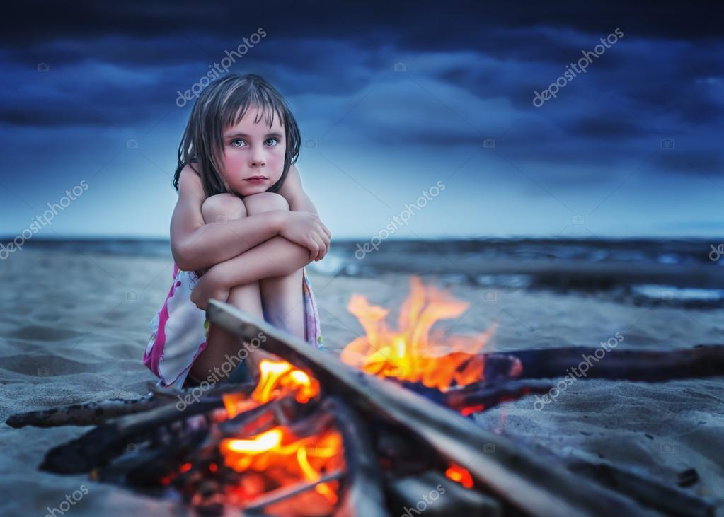 Little girl is heated by the fire.