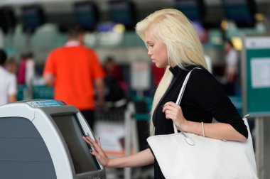 Woman using self check-in kiosk