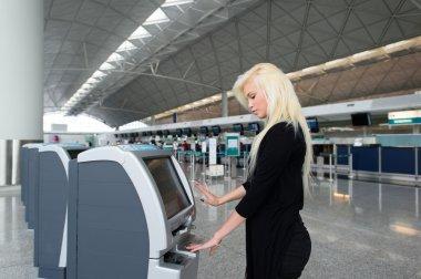 Woman using self check-in kiosk