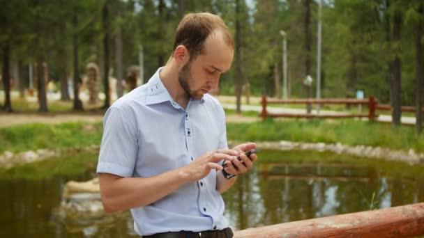 Mann mit mobilen Smartphone im Park, Iphon Stil