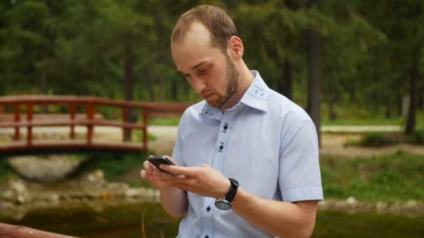 Muž chytrý mobilní telefon v parku, iphon styl.