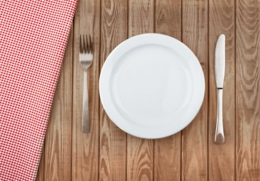 white plate and fork on old wooden table with red cloth